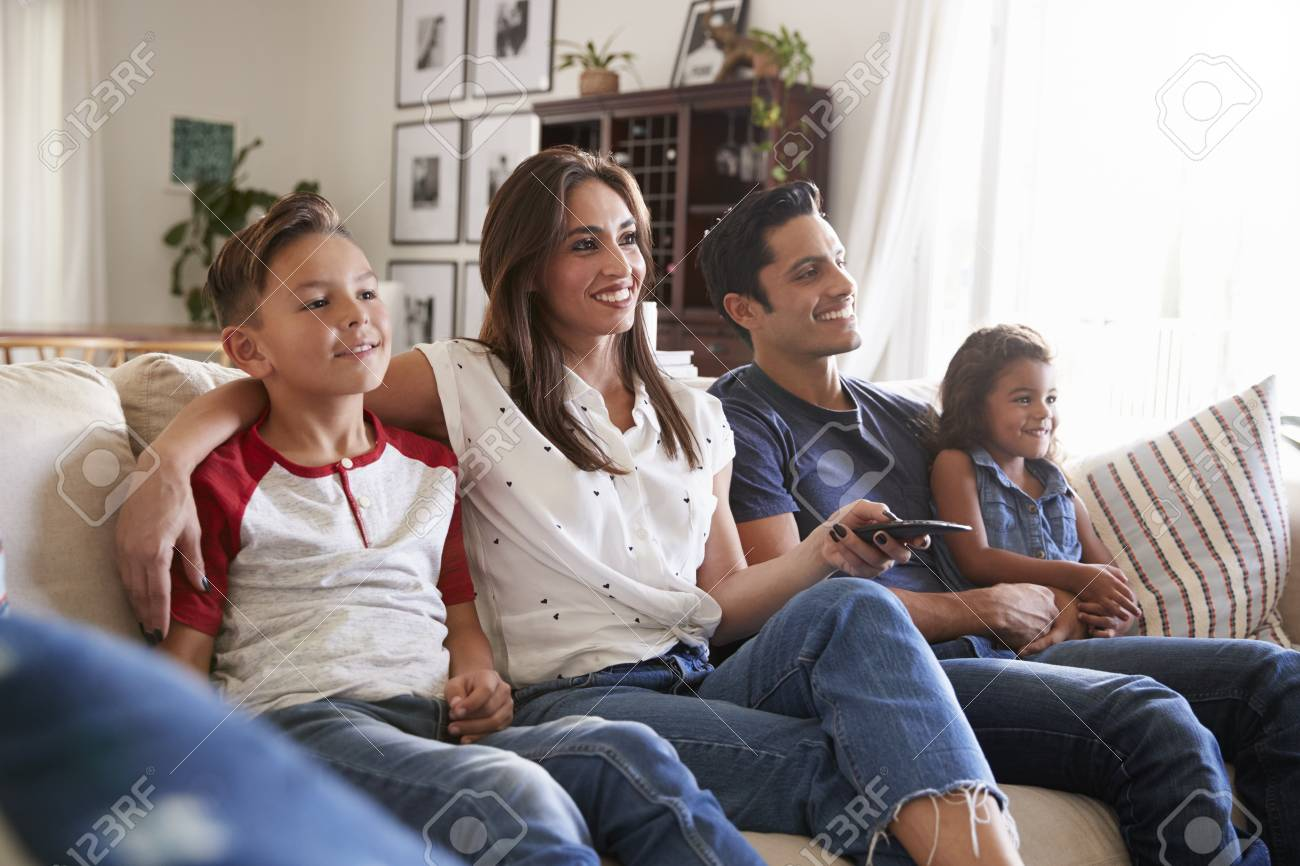 Young Hispanic family sitting on the sofa at home watching TV togther, close up - 115390802