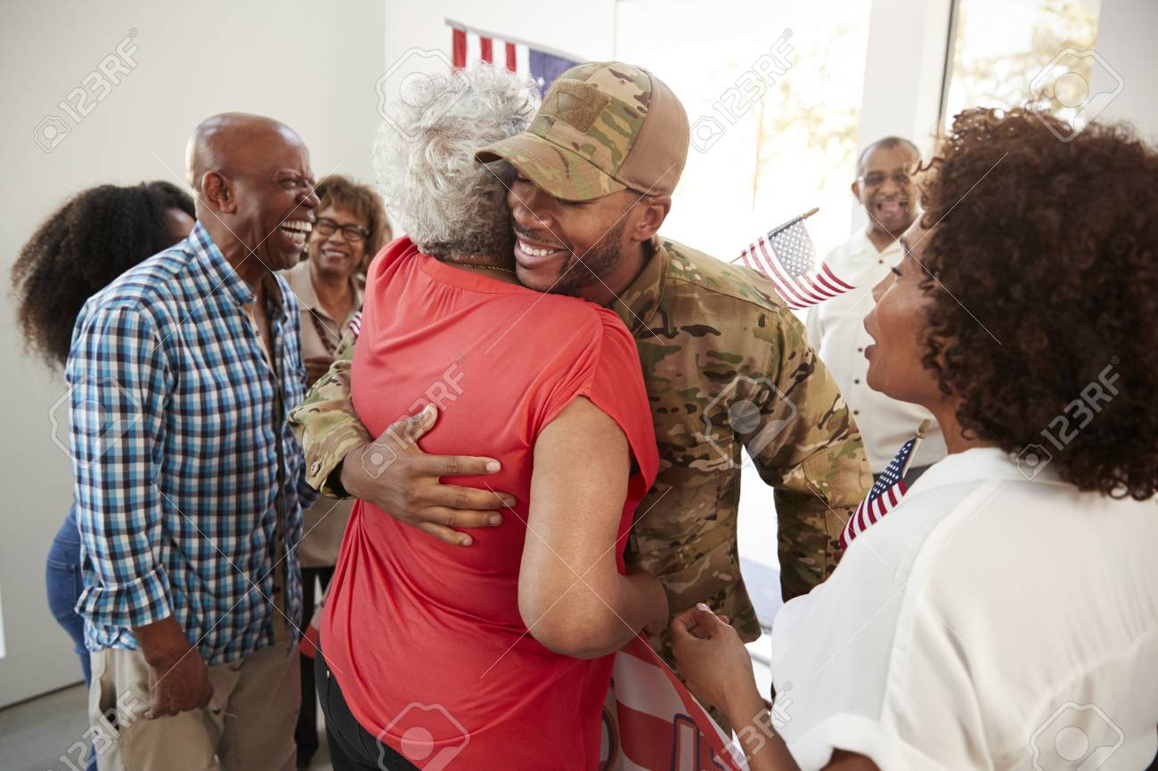Millennial black soldier returning home to family embracing his grandmother,close up - 119507645