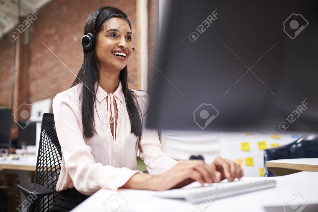 Female Customer Services Agent Working At Desk In Call Center - 120543774