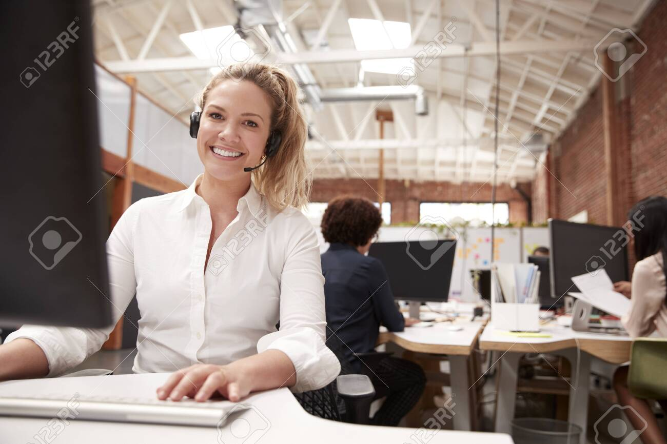 Portrait Of Female Customer Services Agent Working At Desk In Call Center - 120543789