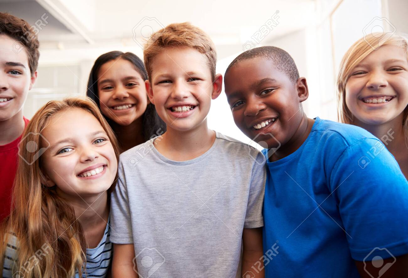Portrait Of Smiling Male And Female Students In Grade School Classroom - 124373273