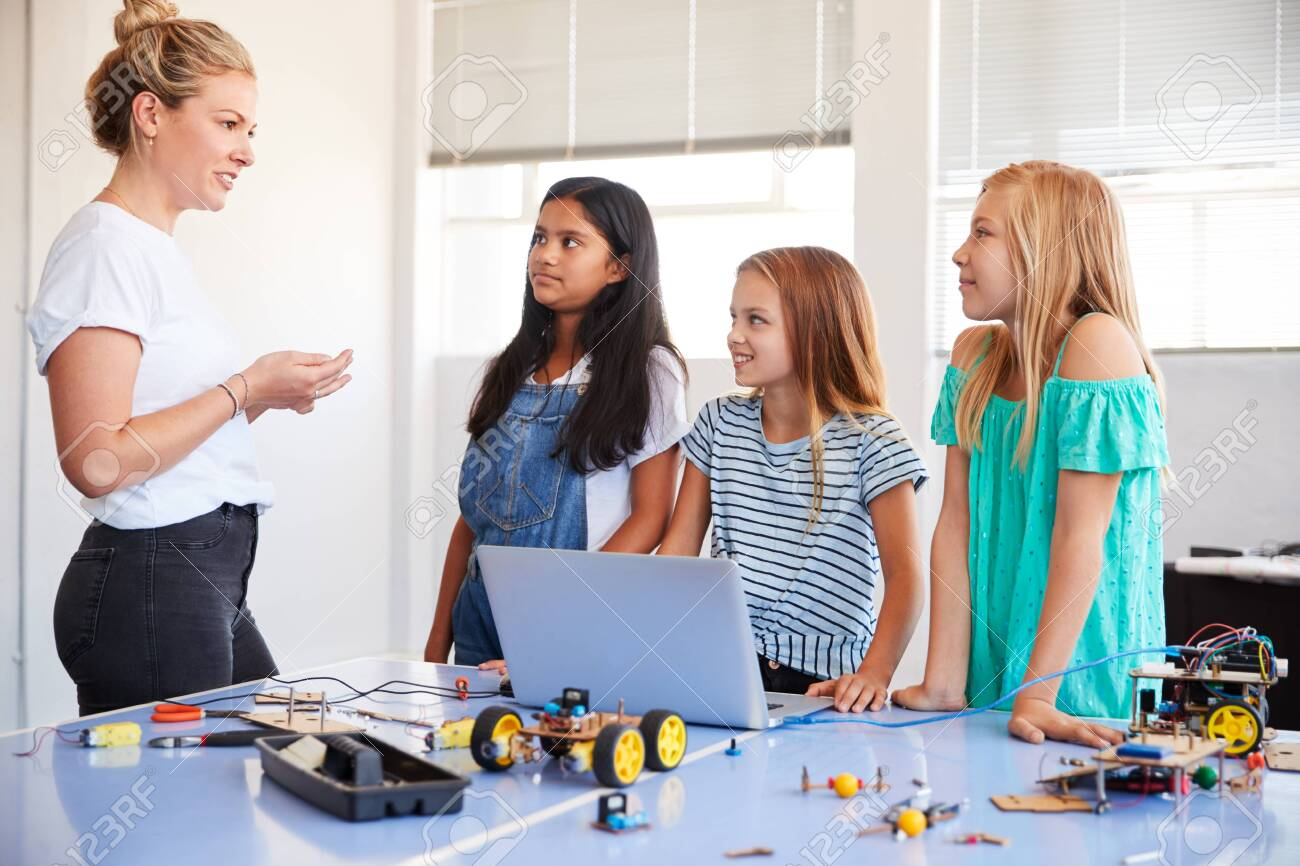 Three Female Students With Teacher Building Robot Vehicle In After School Computer Coding Class - 124373424