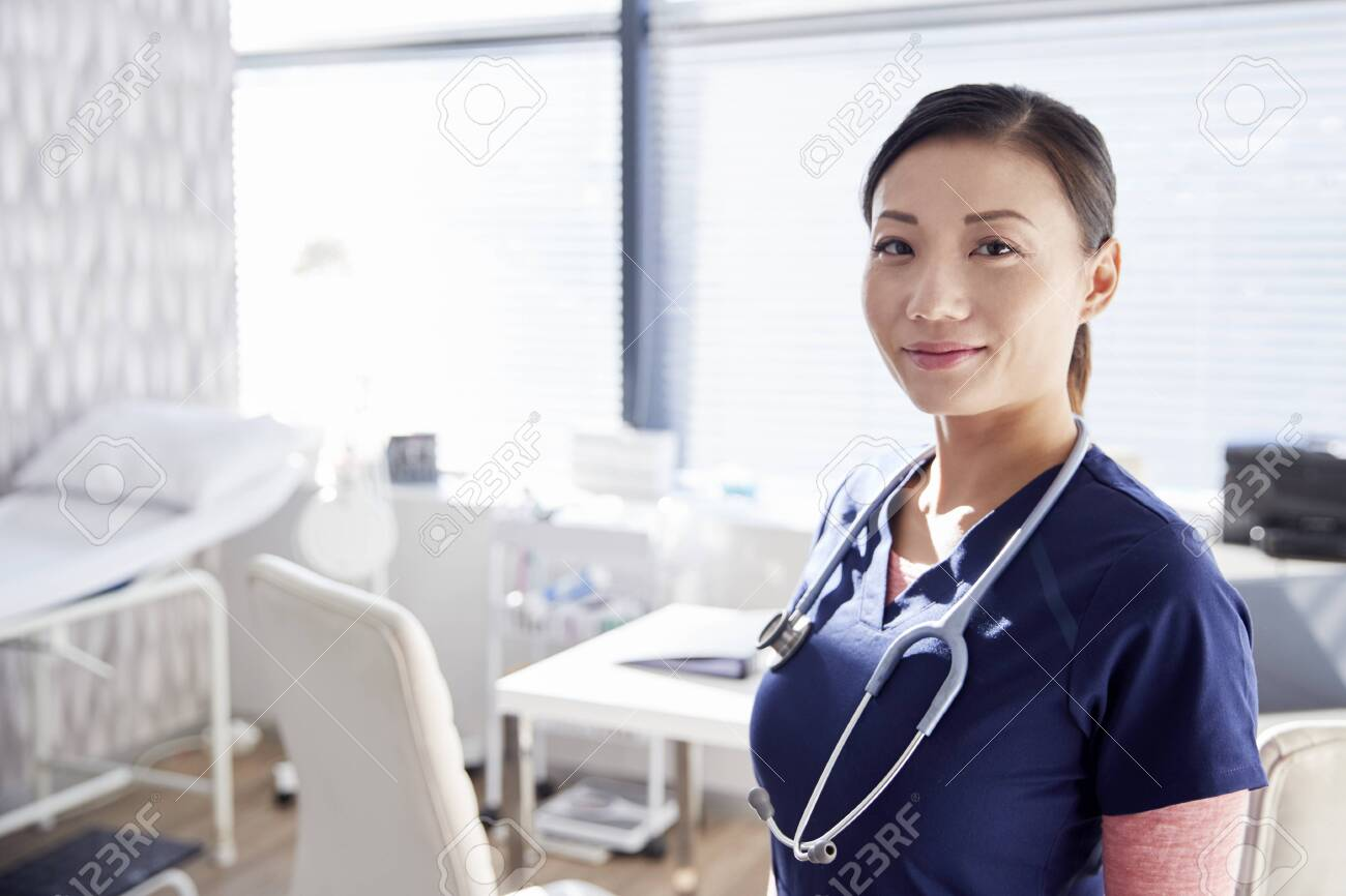 Portrait Of Smiling Female Doctor With Stethoscope Standing By Desk In Office - 124373802