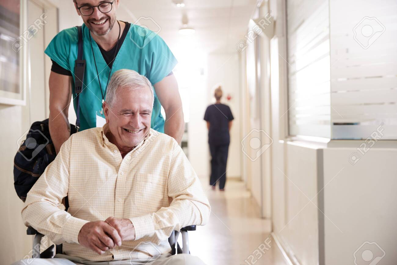 Male Orderly Pushing Senior Male Patient Being Discharged From Hospital In Wheelchair - 124373859