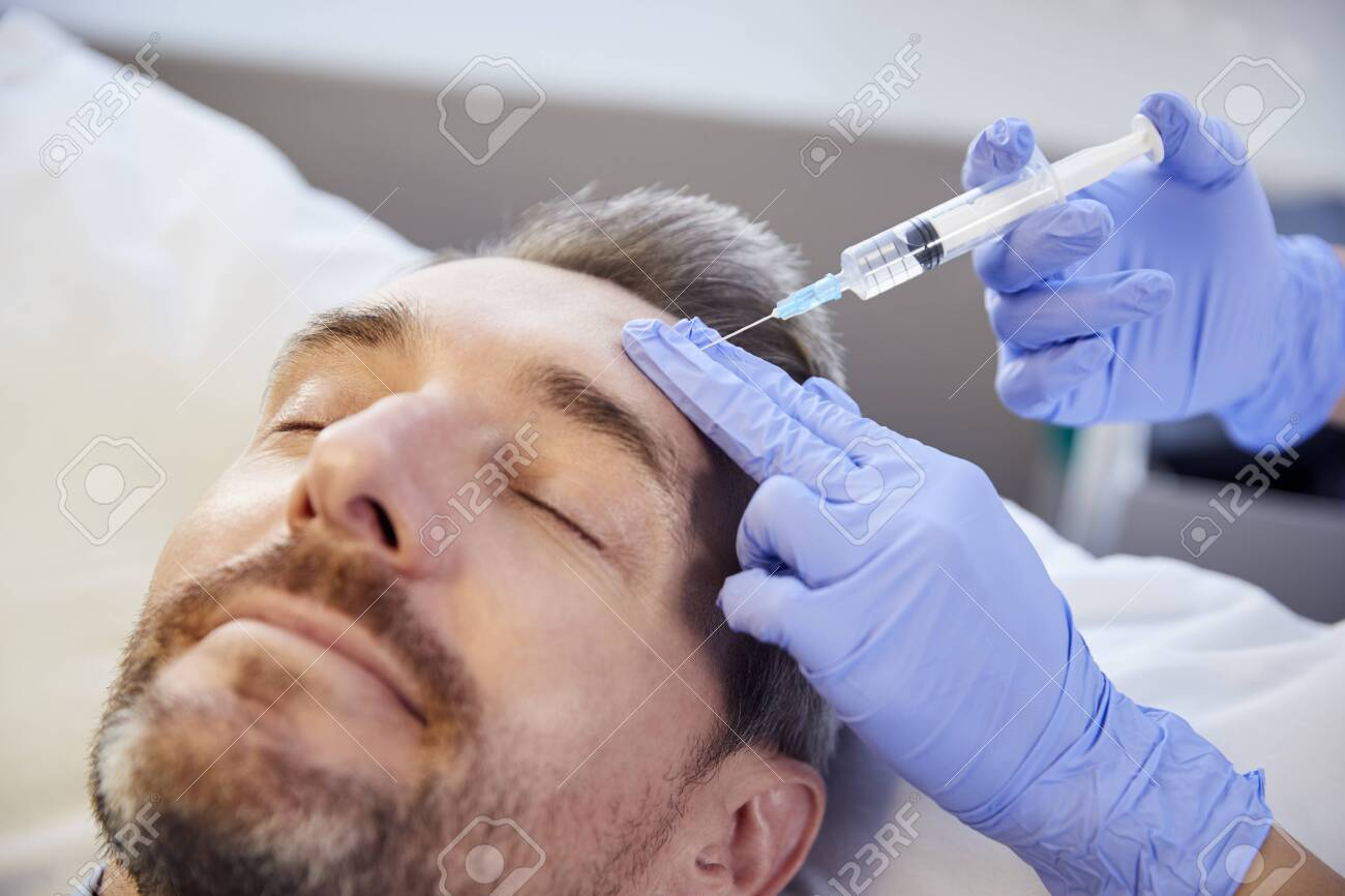 Female Beautician Giving Mature Male Patient Botox Injection In Forehead - 124373974