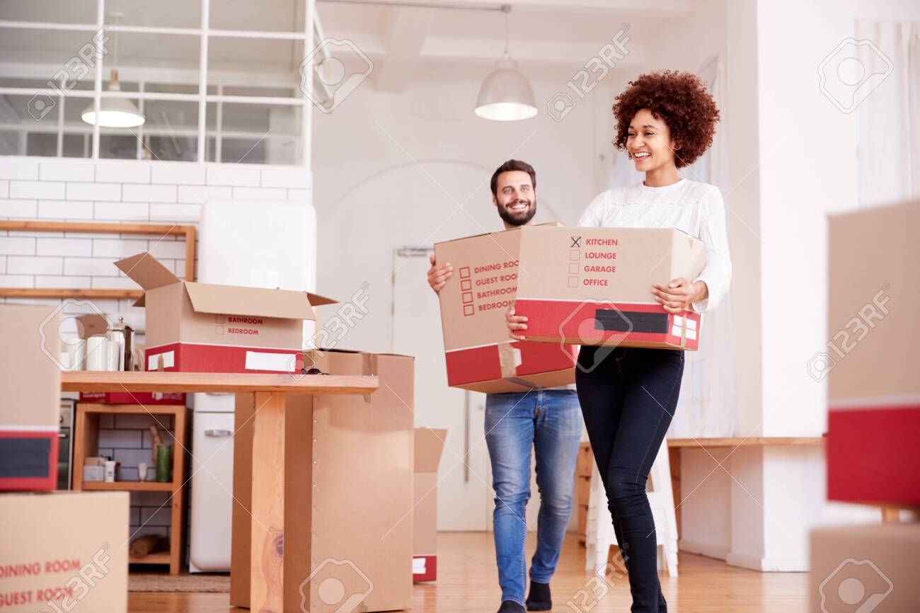 Smiling Couple Carrying Boxes Into New Home On Moving Day - 124542396
