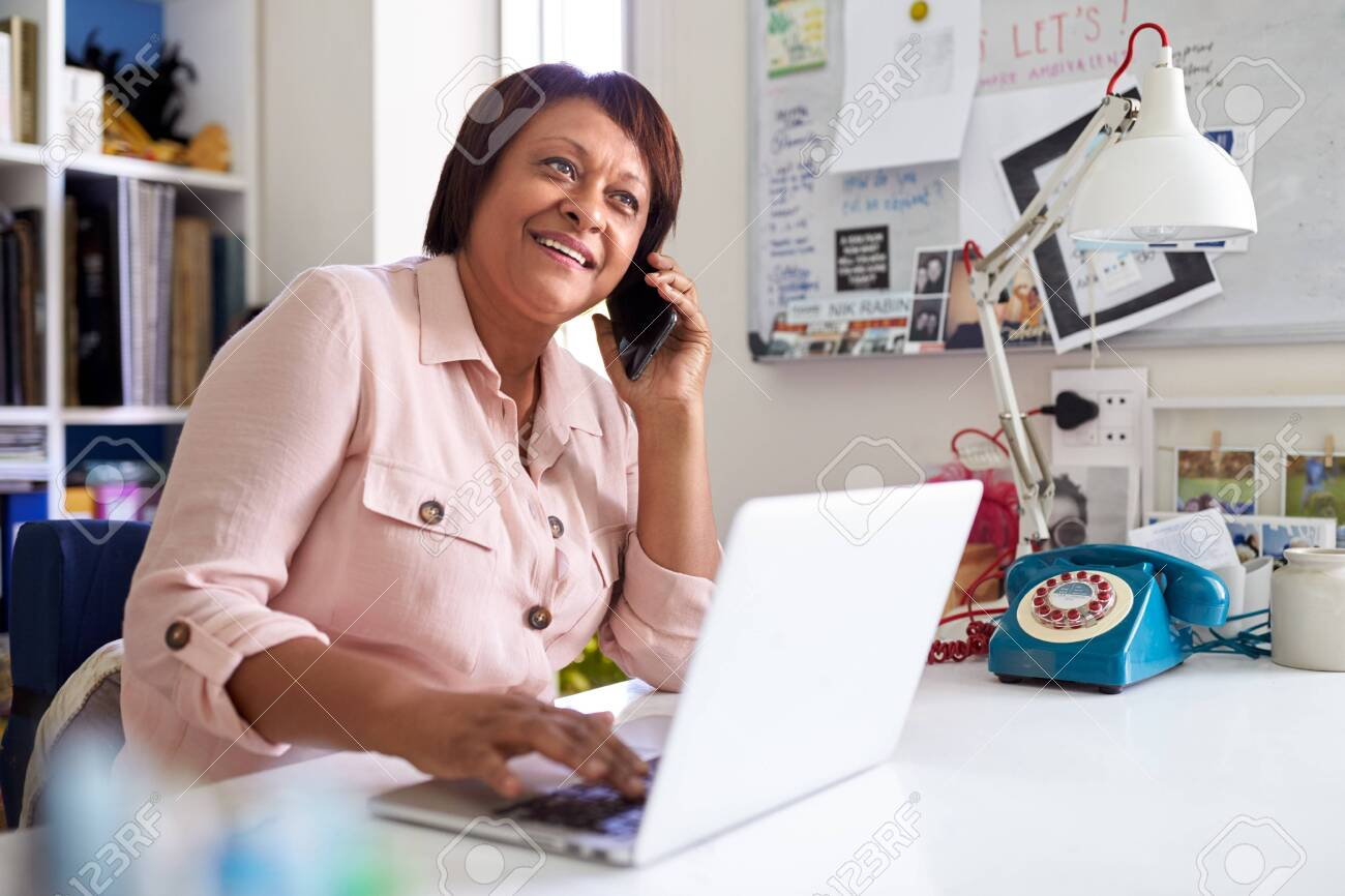 Mature Woman With Laptop Working In Home Office Using Mobile Phone - 125114837