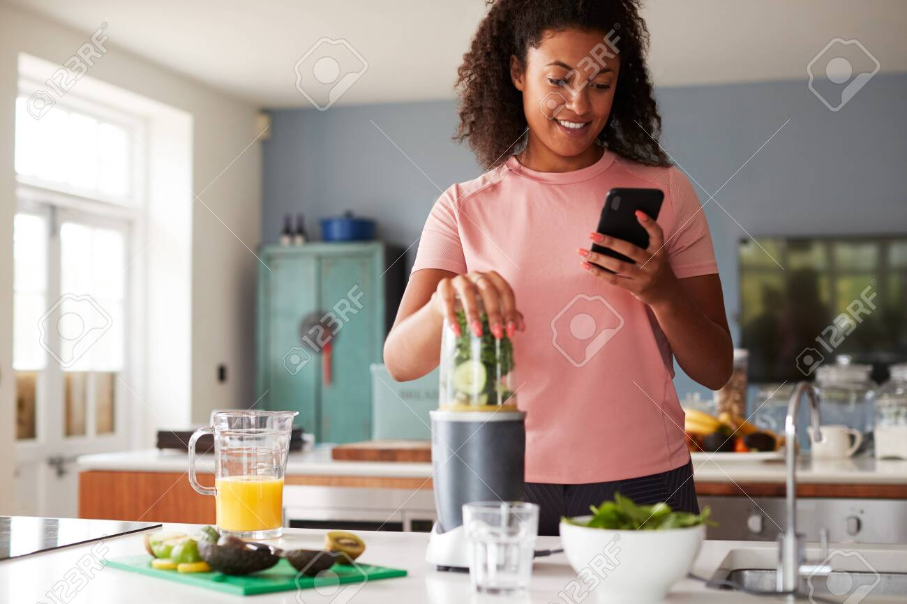 Woman Using Fitness Tracker To Count Calories For Post Workout Juice Drink He Is Making - 128229590