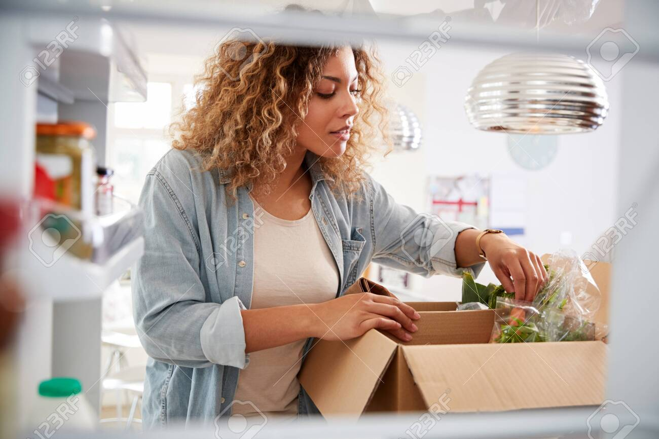View Looking Out From Inside Of Refrigerator As Woman Unpacks Online Home Food Delivery - 128230386