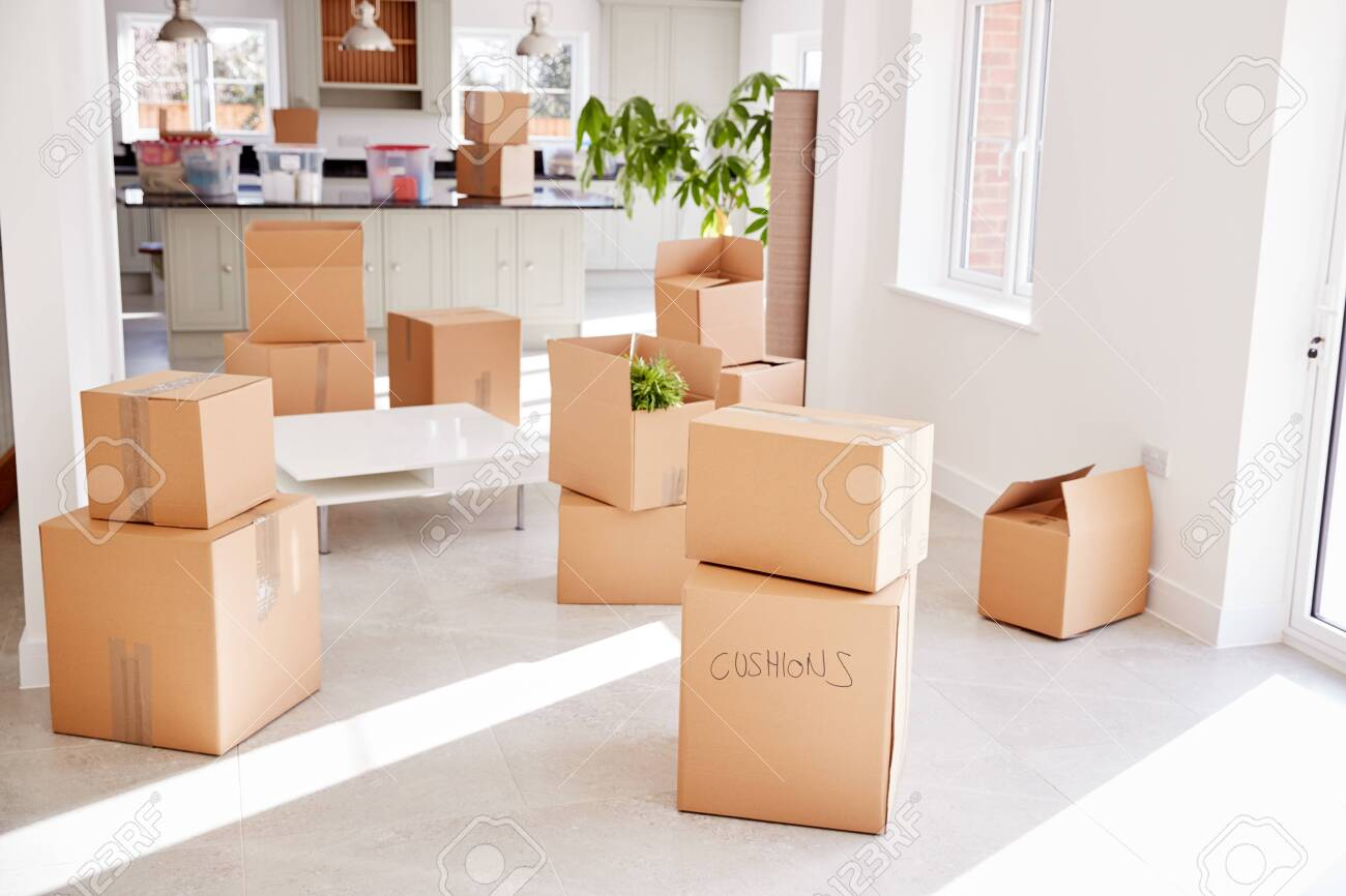 Stacked Removal Boxes In Empty Room On Moving Day - 128563161