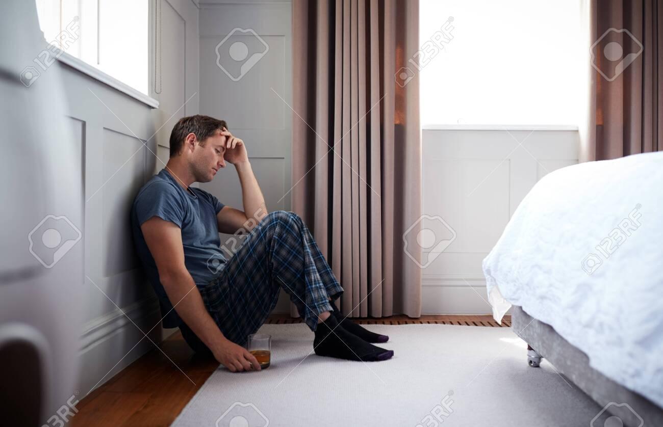 Depressed Man Wearing Pajamas Sitting On Floor Of Bedroom Holding Glass Of Whisky - 129666433