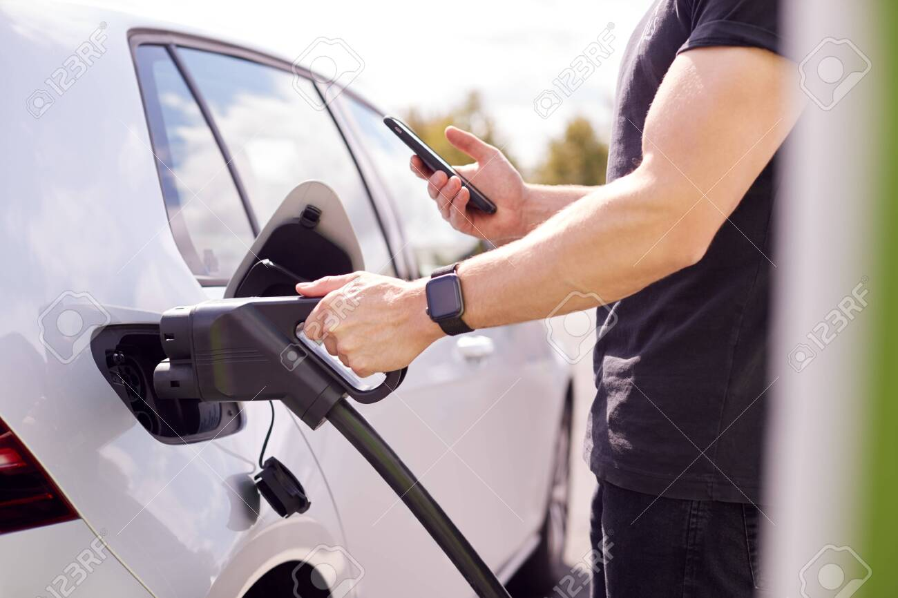 Man Charging Electric Vehicle With Cable Looking At App On Mobile Phone - 129978674