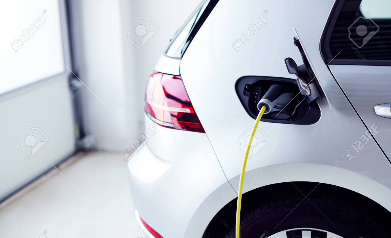 Close Up Of Power Cable Charging Environmentally Friendly Zero Emission Electric Car In Garage - 129978781
