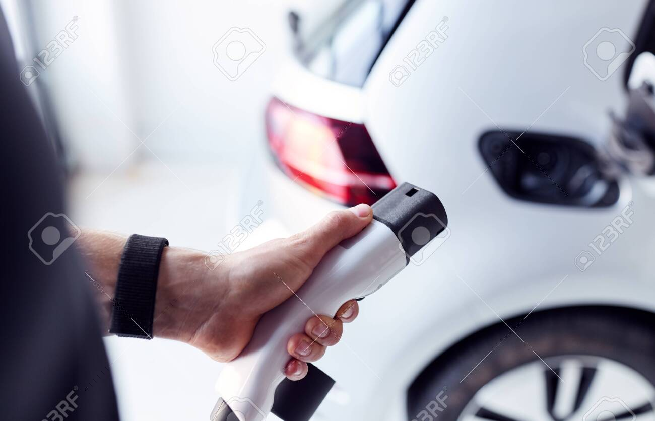 Close Up Of Hand Attaching Power Cable To Environmentally Friendly Zero Emission Electric Car - 129978805