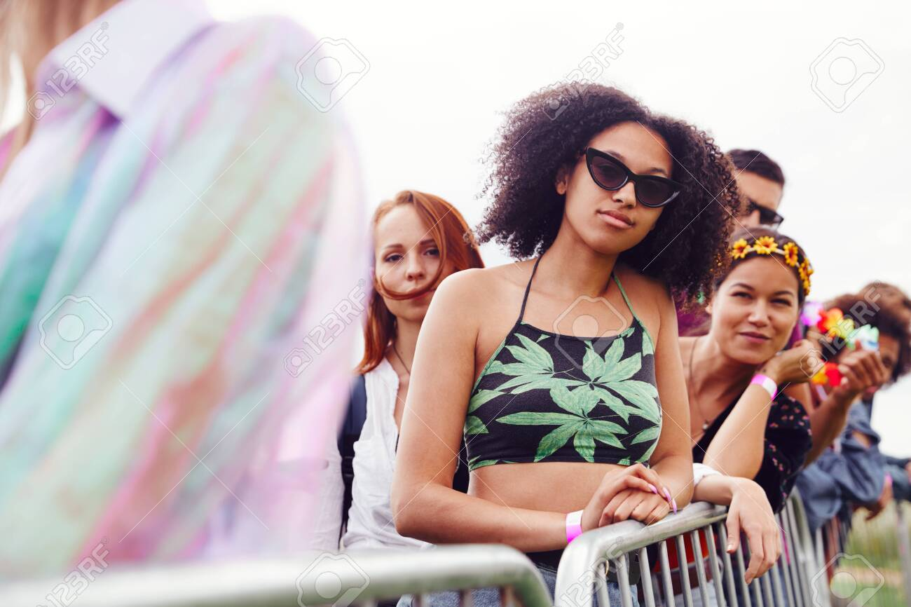 Group Of Young Friends Waiting Behind Barrier At Entrance To Music Festival Site - 133301198