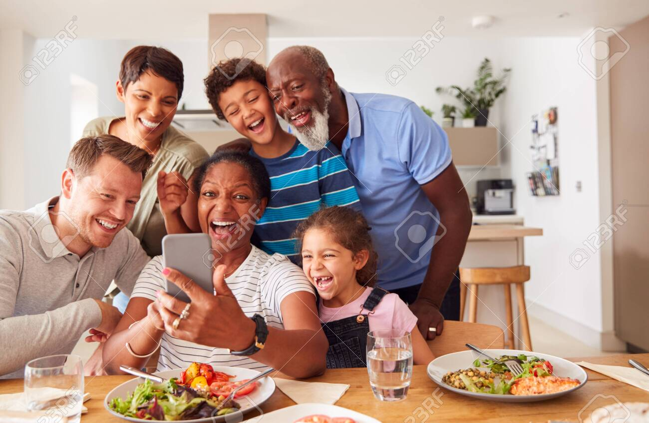 Multi-Generation Mixed Race Family Posing For Selfie As They Eat Meal Around Table At Home Together - 134160143