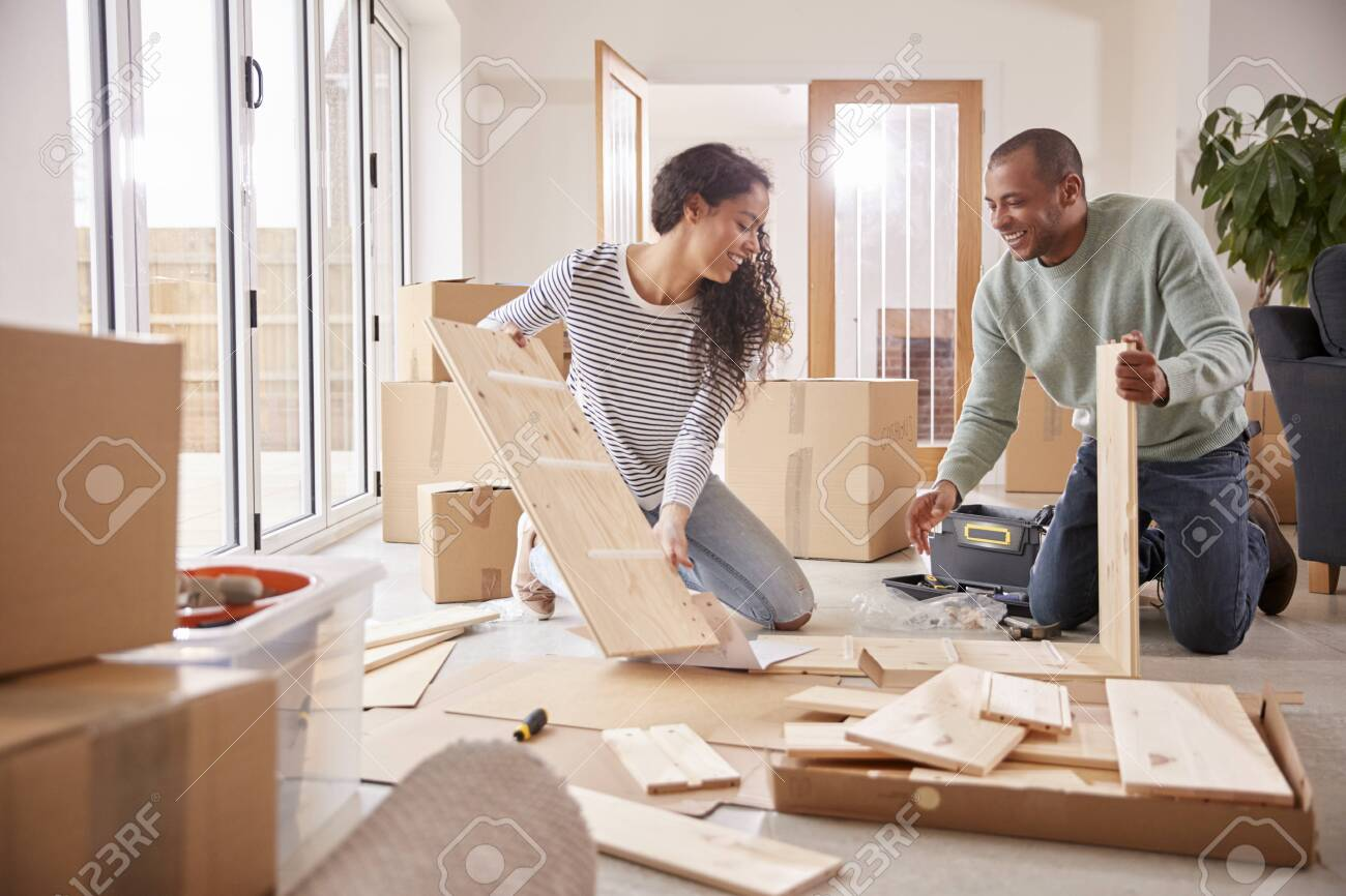 Couple In New Home On Moving Day Putting Together Self Assembly Furniture - 138464497
