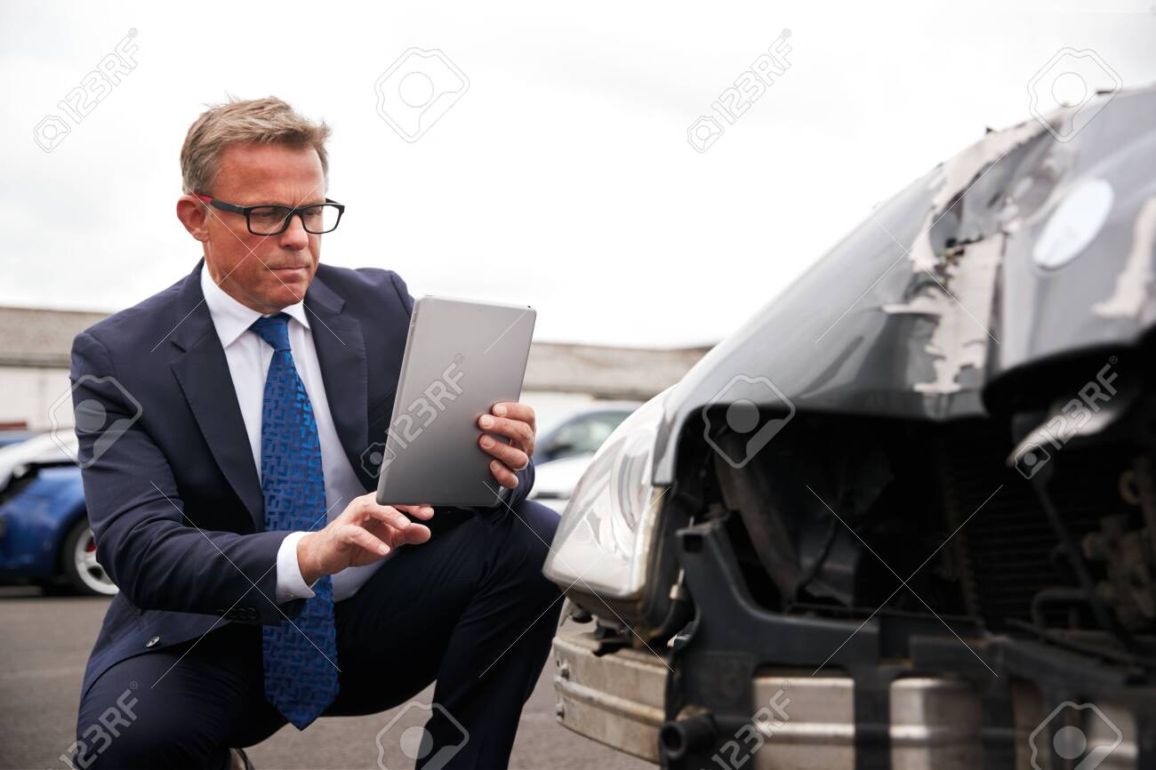 Insurance Loss Adjuster Taking Picture With Digital Tablet Of Damage To Car From Motor Accident - 138464755