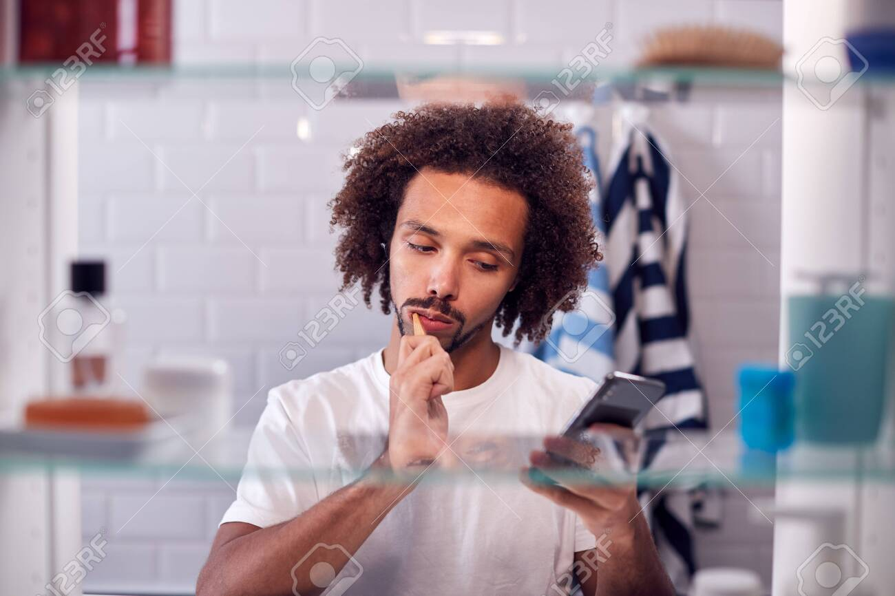 View Through Bathroom Cabinet Of Man Brushing Teeth And Checking Phone Before Going To Work - 141857892