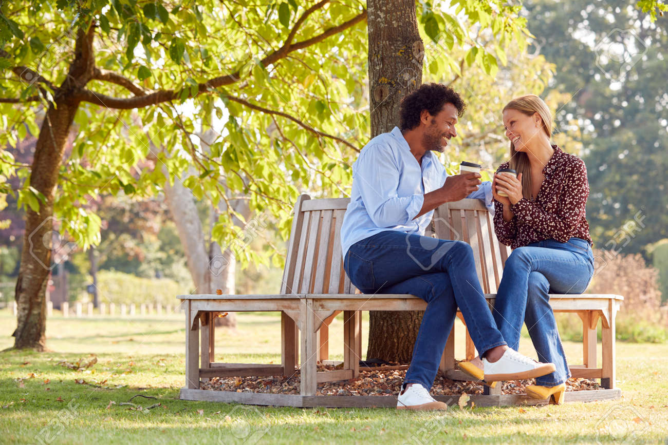 Loving Mature Couple Relaxing Sitting Together On Bench Under Tree In Summer Park With Coffee - 168150677