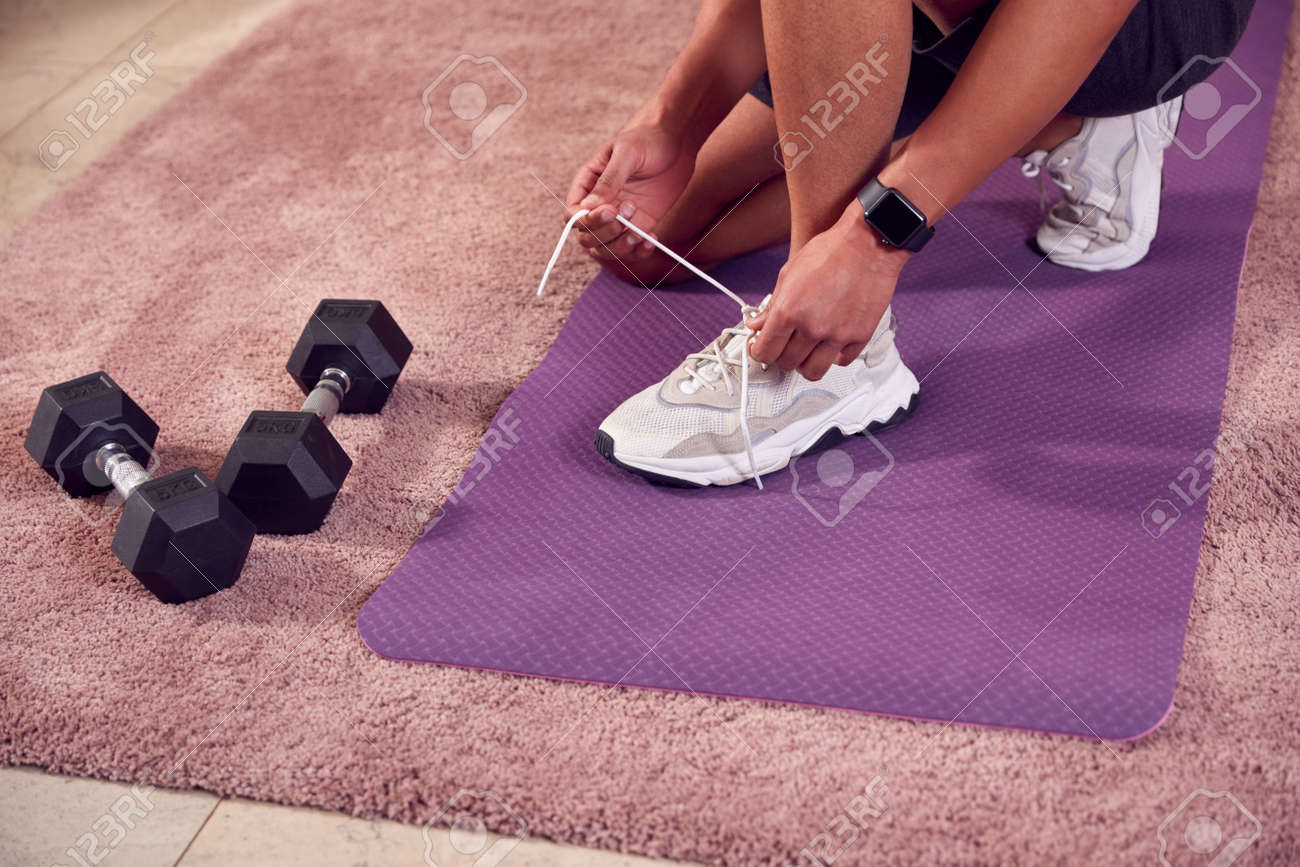 Close Up Of Man In Fitness Clothing At Home Fastening Trainers Before Exercising With Hand Weights - 171585806