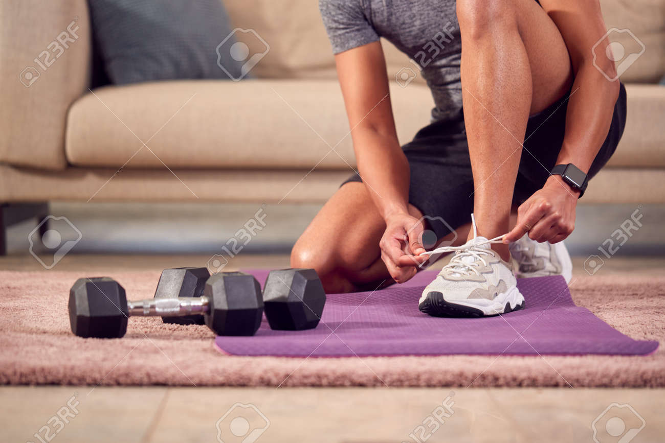 Close Up Of Man In Fitness Clothing At Home Fastening Trainers Before Exercising With Hand Weights - 171585849