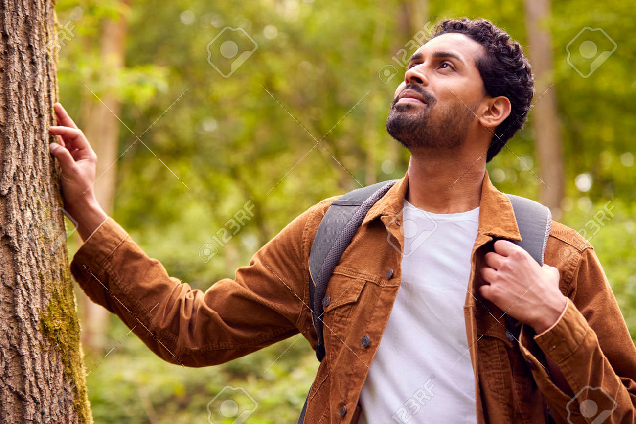 Man Hiking Along Path Through Forest In Countryside Taking A Break And Resting Against Tree - 171585853