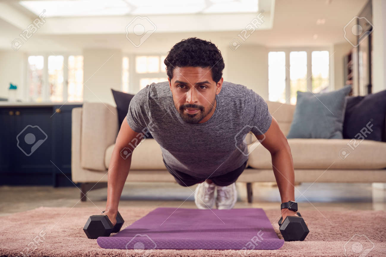 Man In Fitness Clothing At Home In Lounge Exercising With Hand Weights - 171585856
