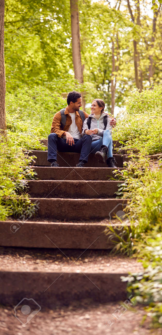 Hiking Couple With Backpacks Sitting On Steps On Path Through Trees In Countryside Together - 171585857
