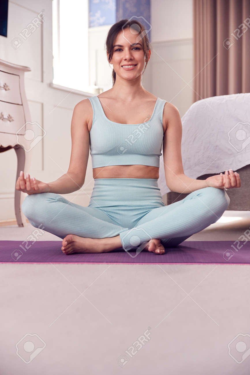 Portrait Of Woman Wearing Fitness Clothing In Bedroom At Home Sitting On Yoga Mat And Meditating - 171585925