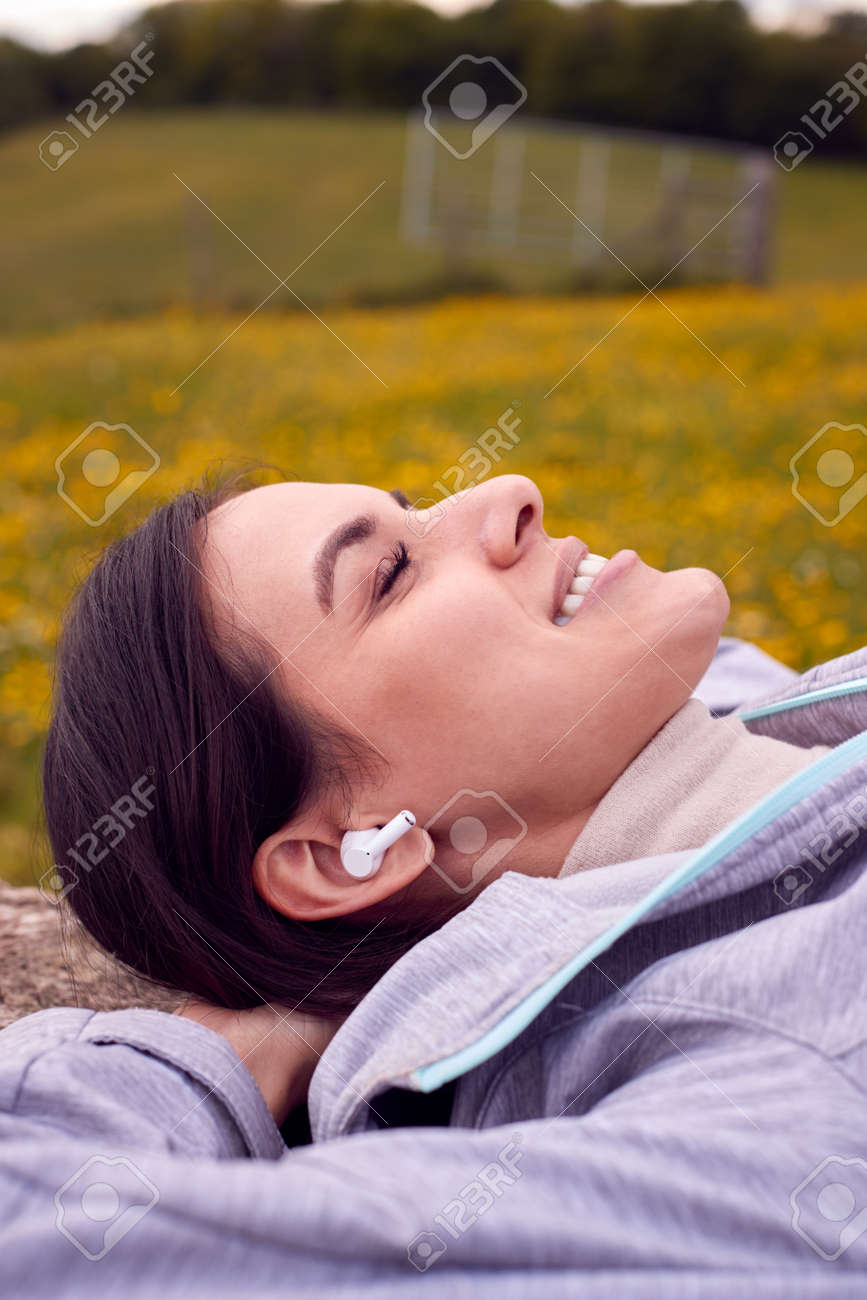 Woman Lying On Bench In Countryside Relaxing And Listening To Music Or Podcast On Wireless Earphones - 171585926