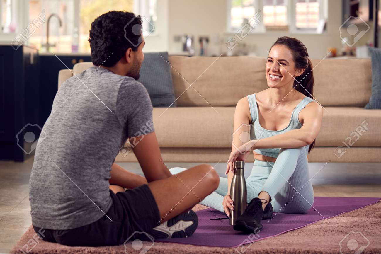 Woman With Male Personal Trainer Exercising At Home Together - 171585928