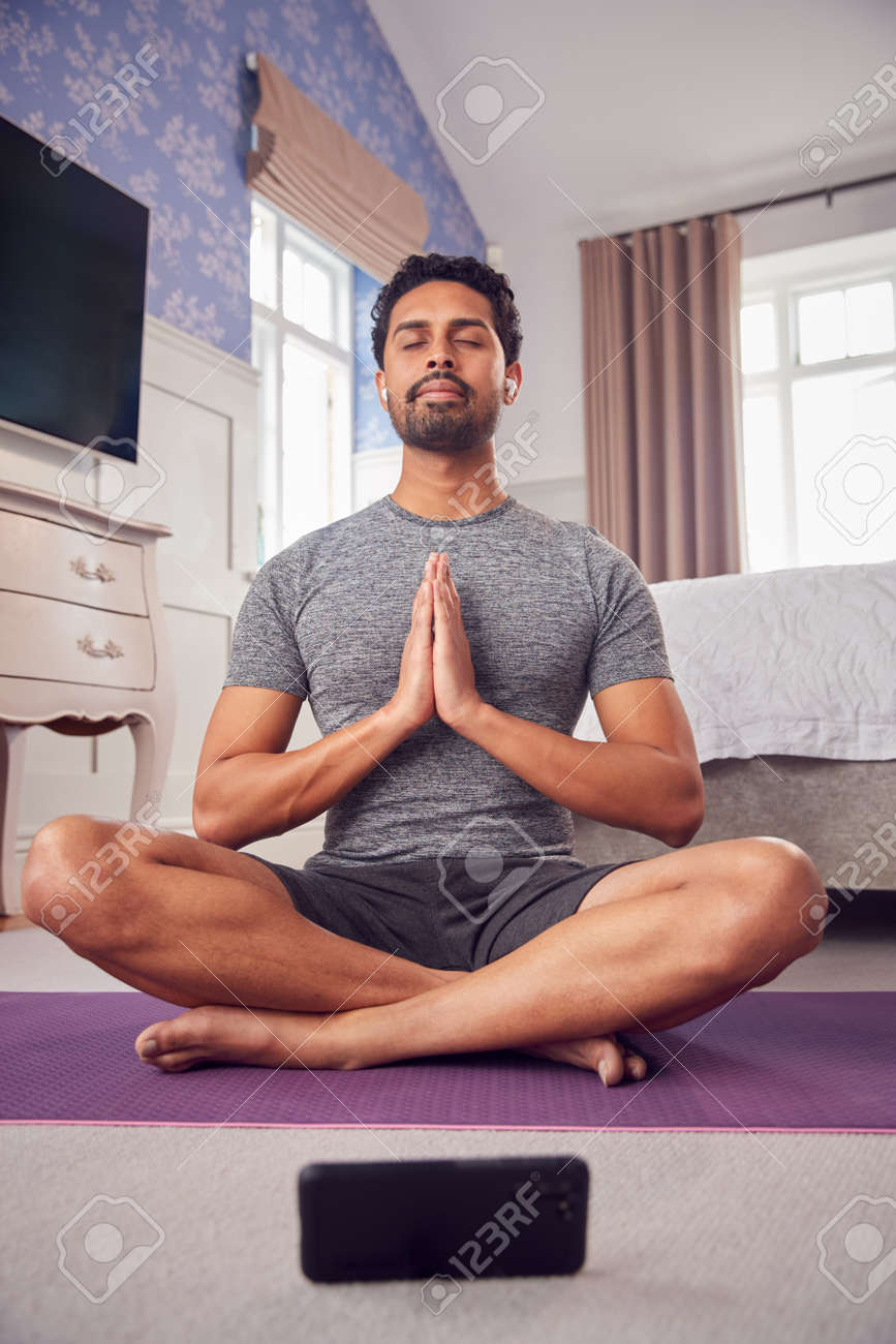 Man In Fitness Clothing In Bedroom At Home On Yoga Mat With Mobile Phone And Wireless Earphones - 171585933