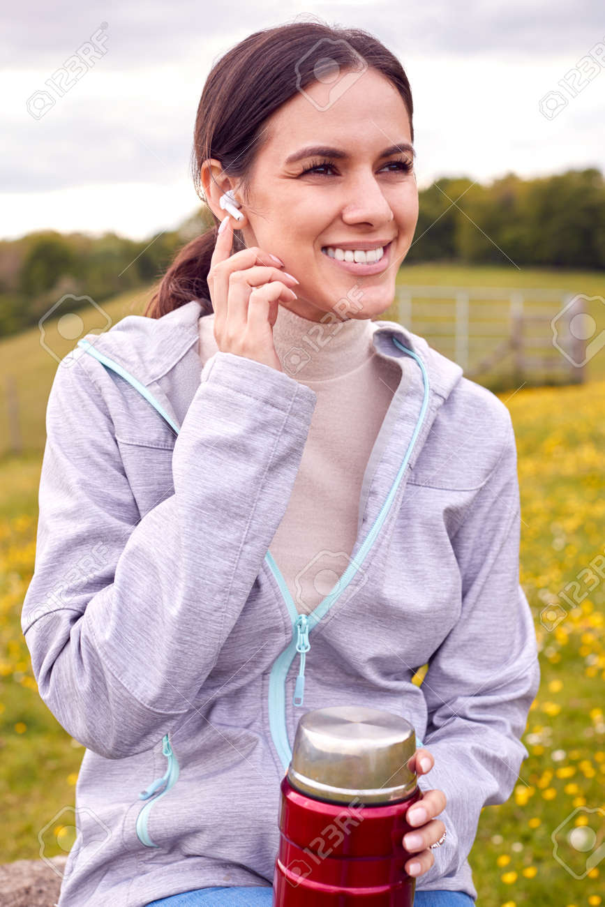 Woman Sitting On Bench In Countryside Relaxing And Listening To Music Or Podcast On Earphones - 171585934