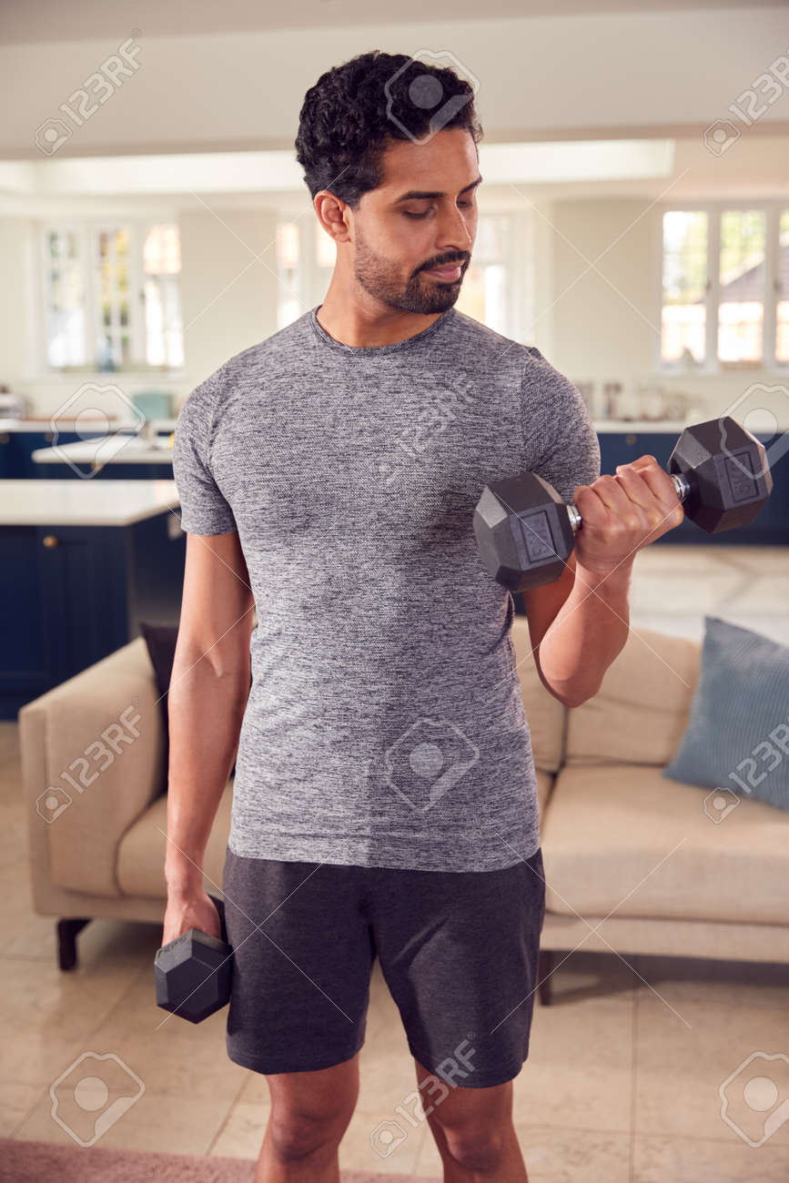 Man In Fitness Clothing At Home In Lounge Exercising With Hand Weights - 171585936