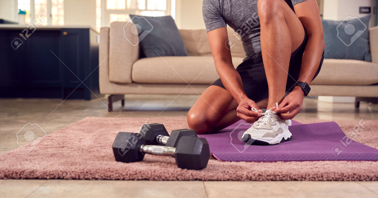 Close Up Of Man In Fitness Clothing At Home Fastening Trainers Before Exercising With Hand Weights - 171585938