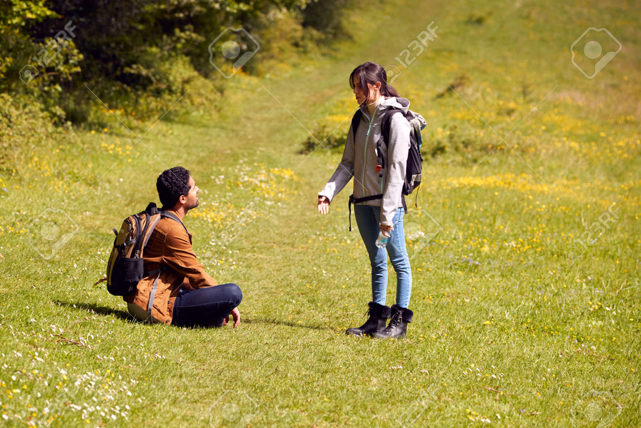 Couple With Backpacks Taking A Break On Hike Along Path Across Field By Forest In Countryside - 171585939