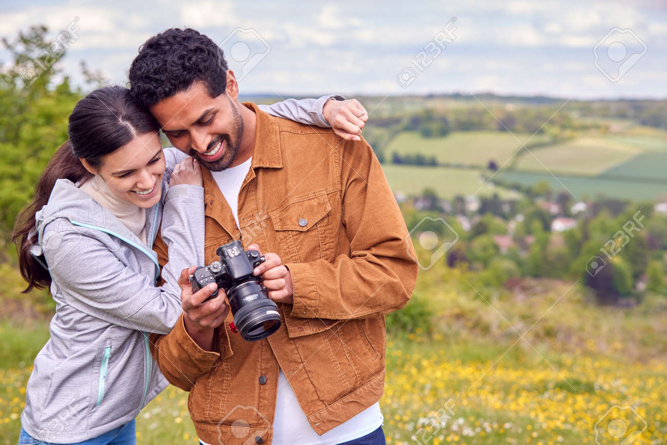 Couple With Digital DSLR Camera Taking Photos In Countryside Together - 171585944