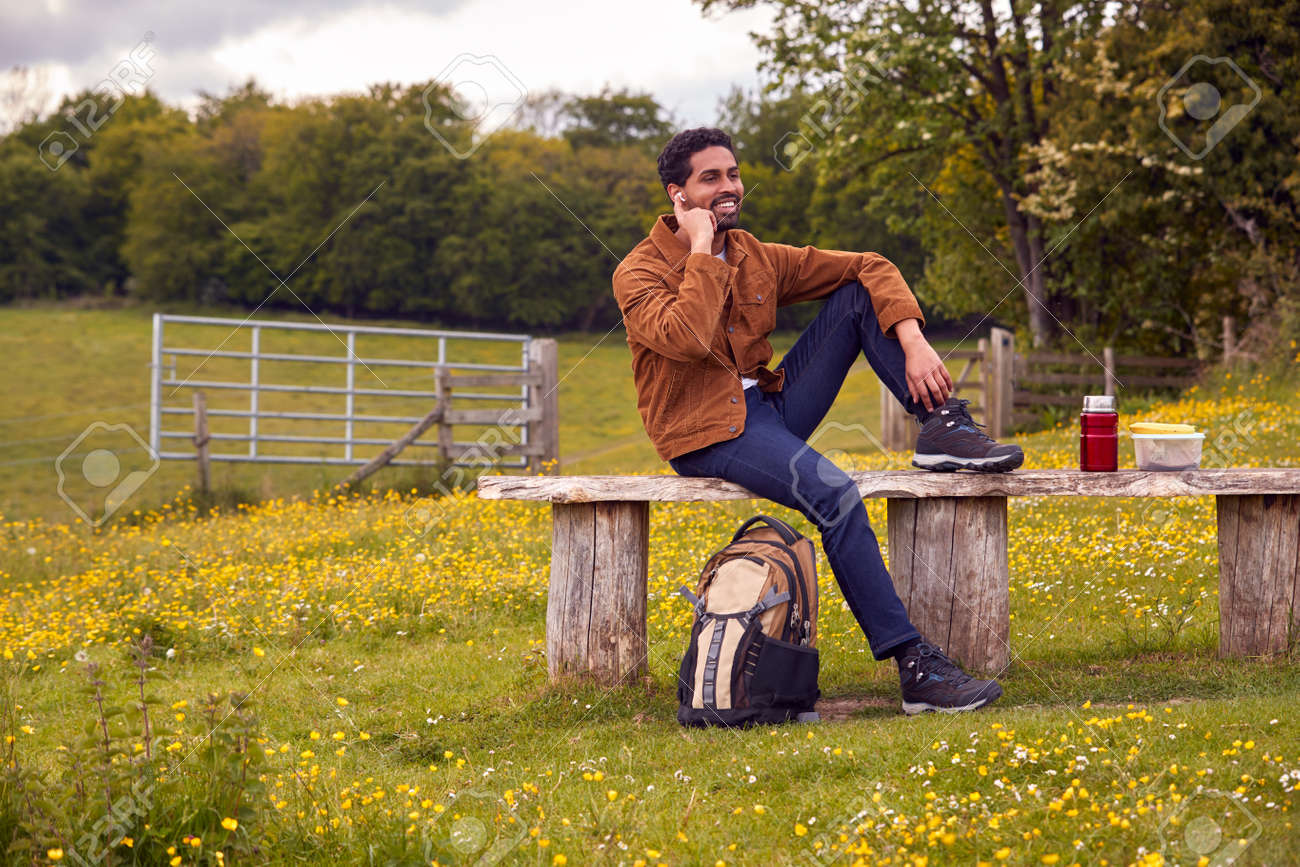 Man Sitting On Bench In Countryside Relaxing And Listening To Music Or Podcast On Wireless Earphones - 171585970