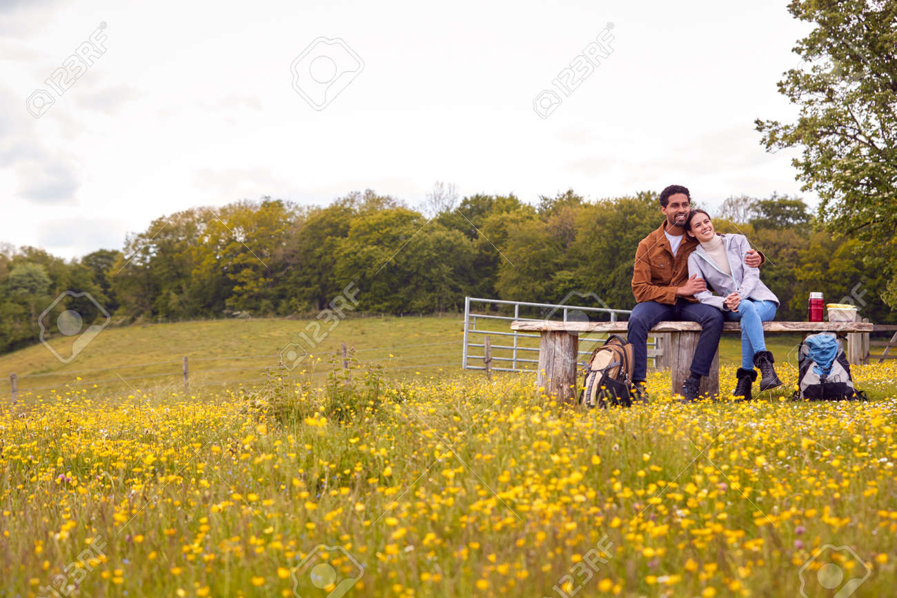 Couple On Walk In Countryside Sit On Bench And Enjoy Picnic Together - 171585971