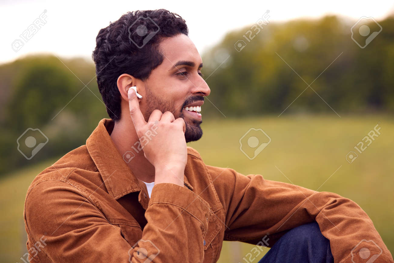 Man Sitting On Bench In Countryside Relaxing And Listening To Music Or Podcast On Wireless Earphones - 171585973