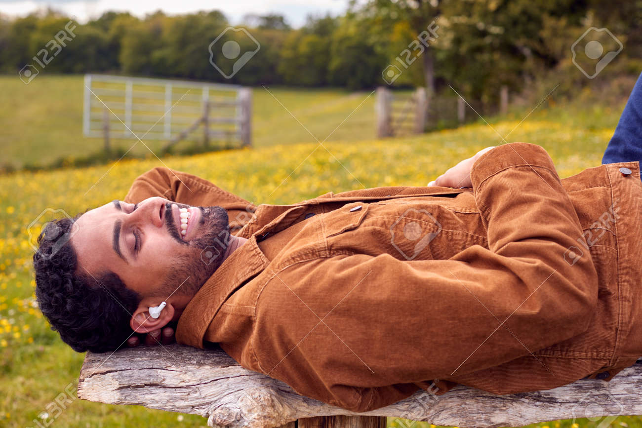 Man Lying On Bench In Countryside Relaxing And Listening To Music Or Podcast On Wireless Earphones - 171585974