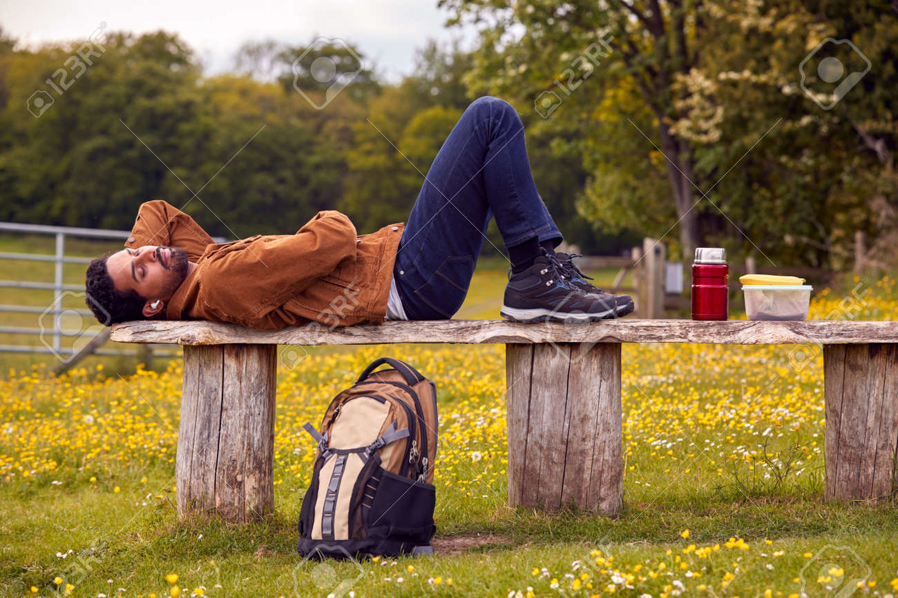Man Lying On Bench In Countryside Relaxing And Listening To Music Or Podcast On Wireless Earphones - 171585976