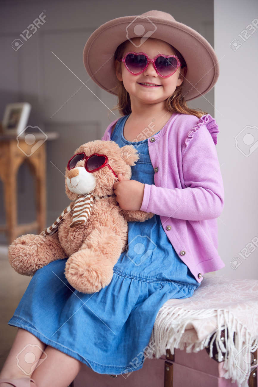 Portrait Of Young Girl Wearing Hat And Sunglasses Having Fun Playing With Dressing Up Box At Home - 172365012