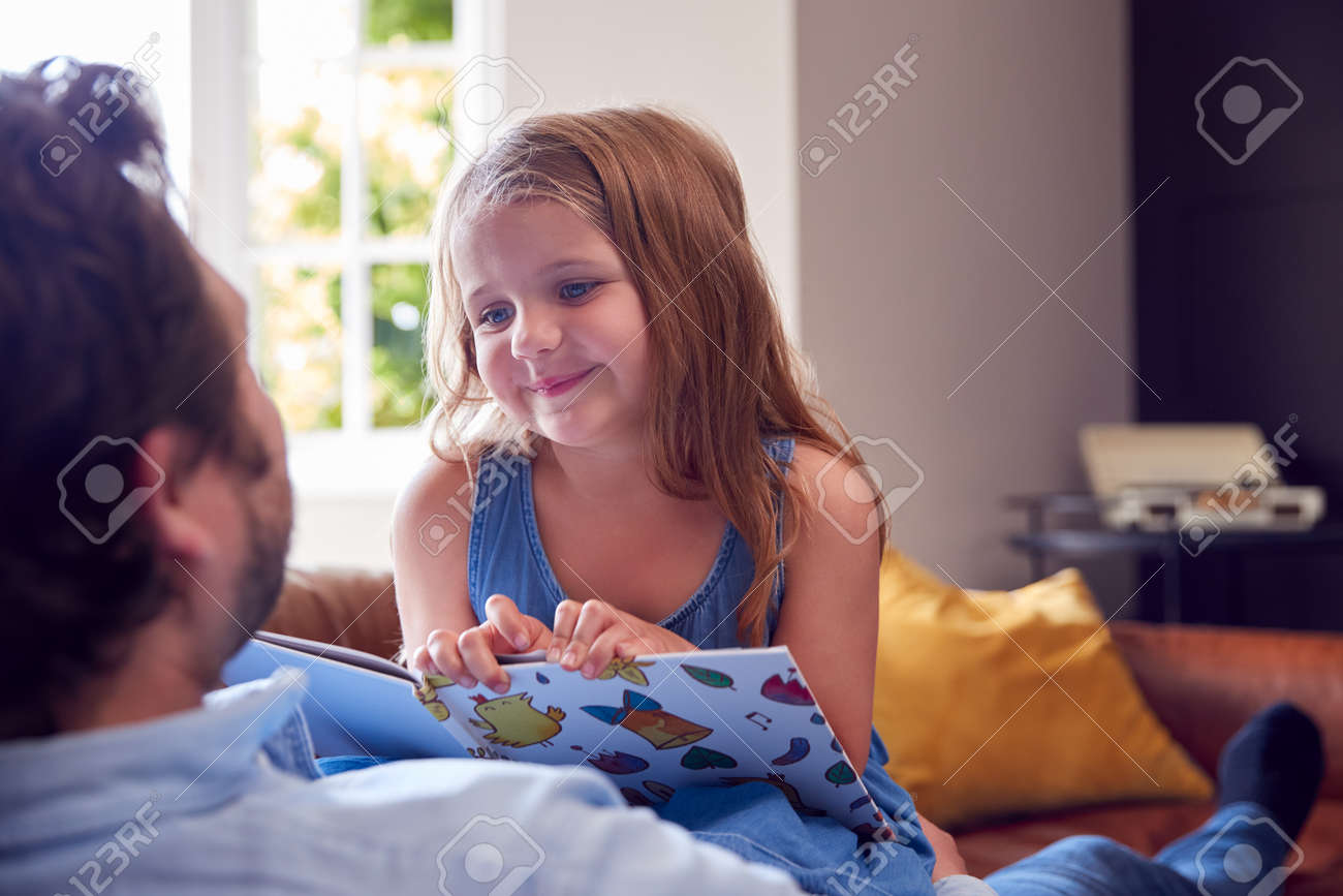 Father And Daughter Lying On Sofa At Home As Girl Reads Book - 172365017