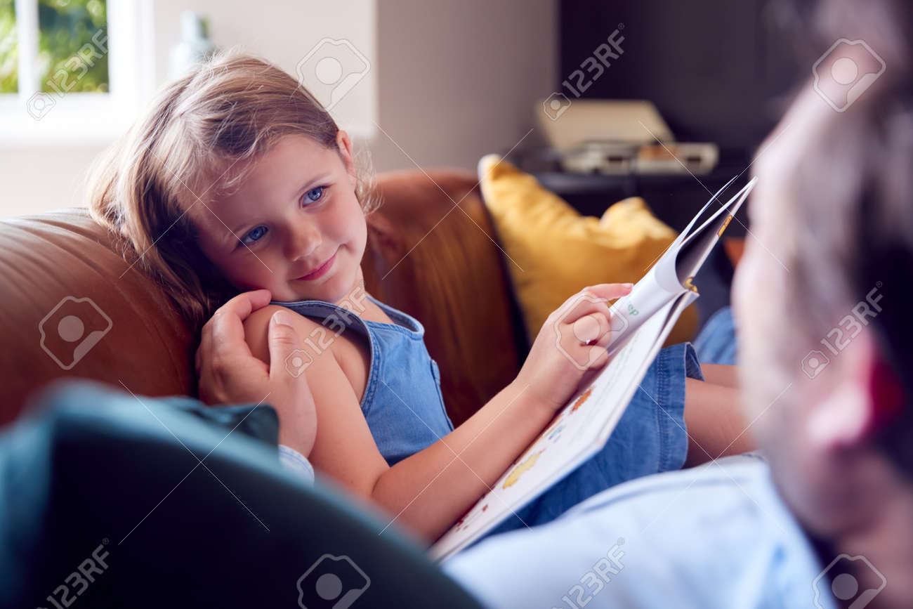 Father And Daughter Lying On Sofa At Home As Girl Reads Book - 172365019