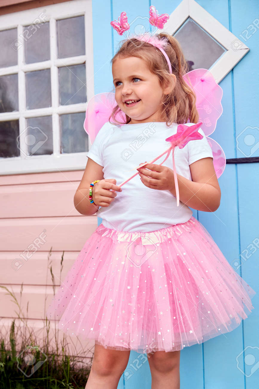 Young Girl Wearing Fairy Costume Playing Outdoors In Garden By Playhouse - 172365022