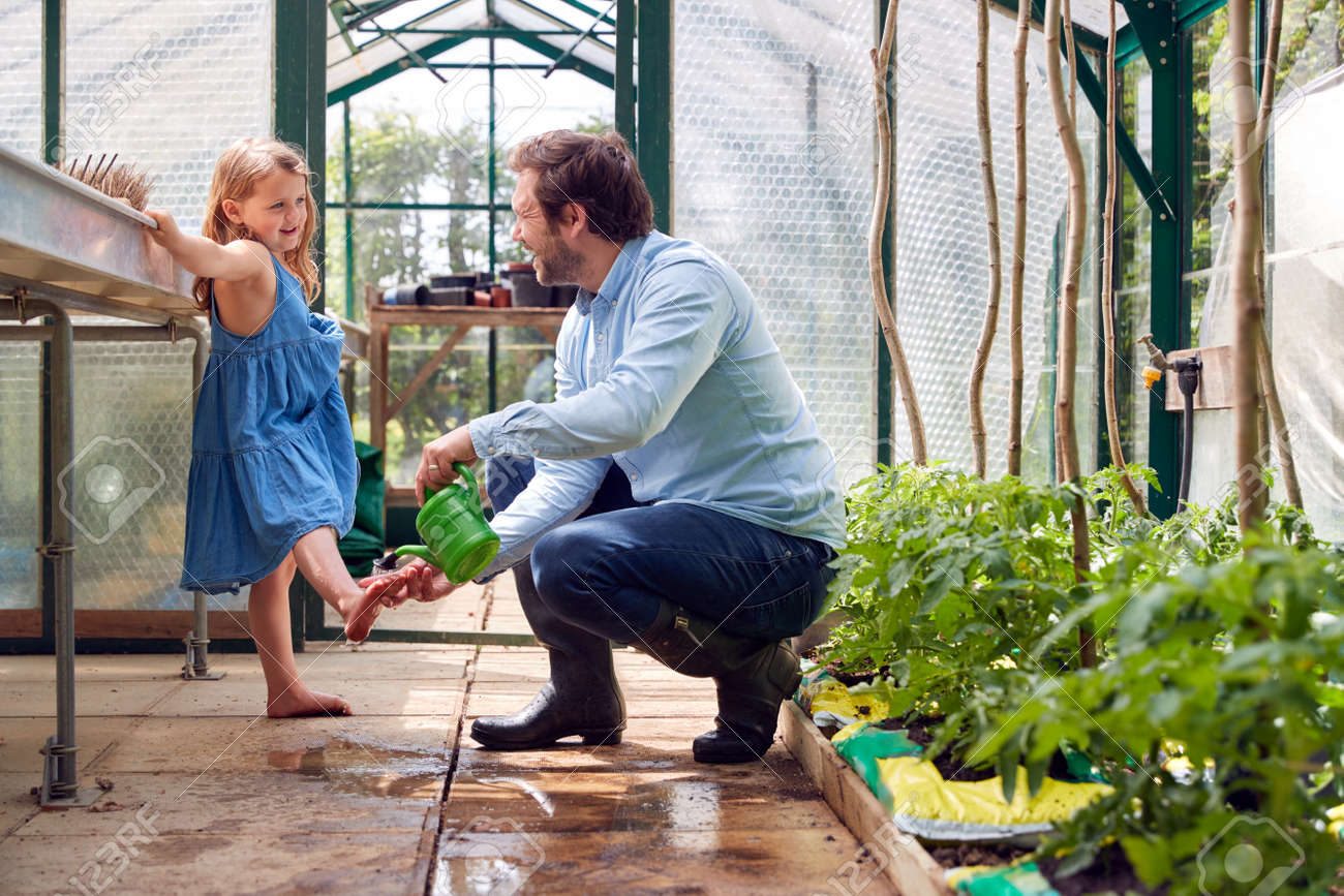 Father Washes Daughter's Feet Using Watering Can As She Helps Him In Greenhouse At Home - 172365032