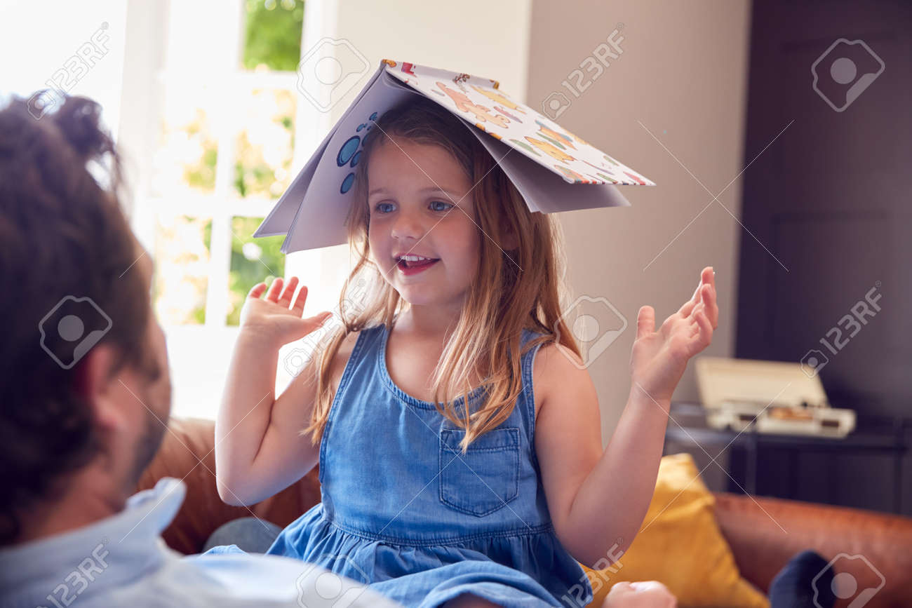 Father And Daughter Lying On Sofa At Home As Girl Puts Reading Book On Head - 172365033