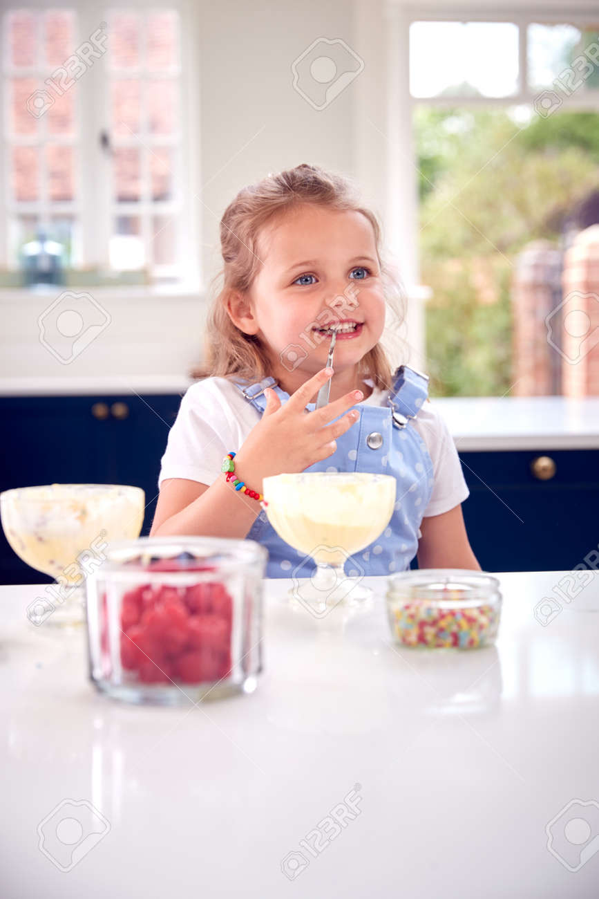 Young Girl In Kitchen Eating Ice Cream Dessert With Spoon - 172365041